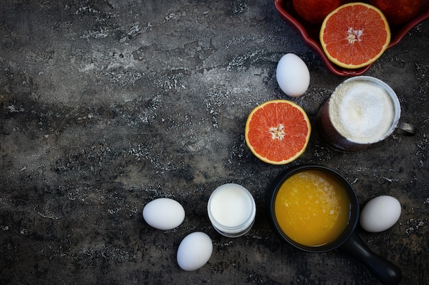 Ingredientes para apoiar o bolo de laranja de sangue no fundo escuro