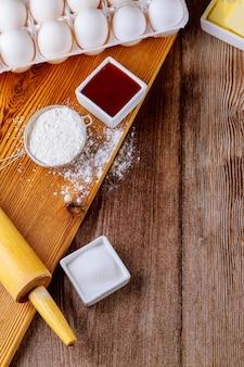 Ingredientes para assar biscoitos de farinha, ovos e açúcar com rolo.