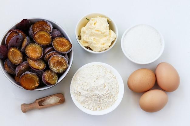 Ingredientes para assar bolo de ameixa em um branco