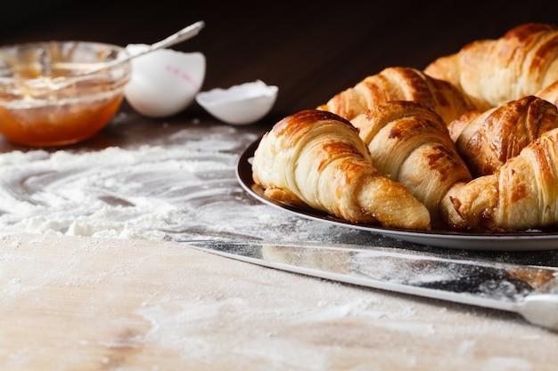 Ingredientes para assar croissants - farinha, colher de pau, rolo, ovos, gemas de ovos