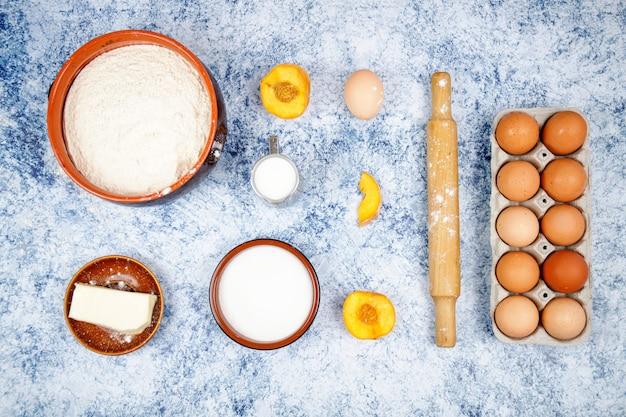 Ingredientes para assar - ovos, farinha, açúcar, manteiga, leite sobre um fundo azul claro de concreto, pedra ou ardósia. vista superior com espaço para texto.