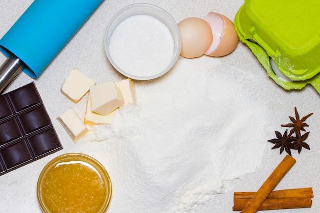 Ingredientes para biscoitos de natal caseiros. ingredientes da receita de massa (ovos, farinha, manteiga, açúcar) na mesa a vista de cima.