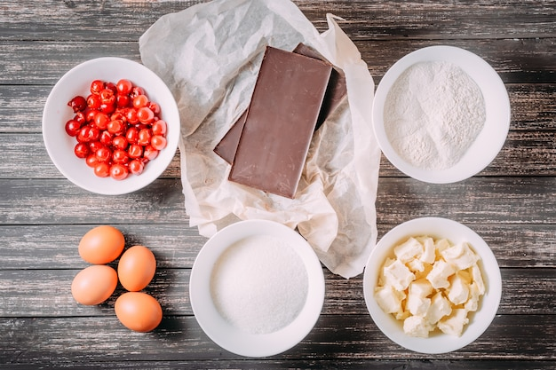 Ingredientes para bolinhos brownie ou bolo de chocolate com cereja na mesa de madeira, vista superior