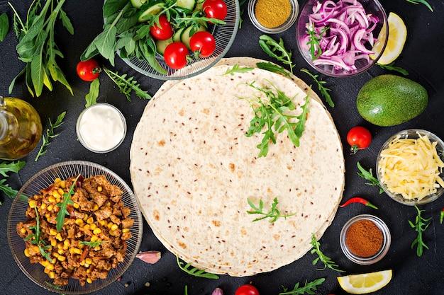 Ingredientes para burritos envolve com carne e legumes no preto. comida mexicana. vista do topo. configuração plana