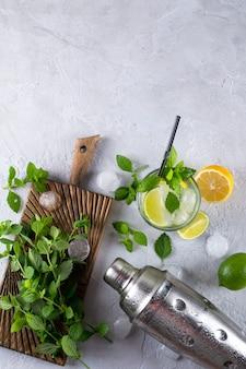 Ingredientes para coquetéis de mojito ou outras bebidas em um fundo cinza de concreto