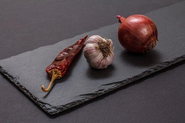 Ingredientes para cozinhar carne ou peixe. alho, pimenta seca e cebola em uma tábua de pedra e fundo preto.