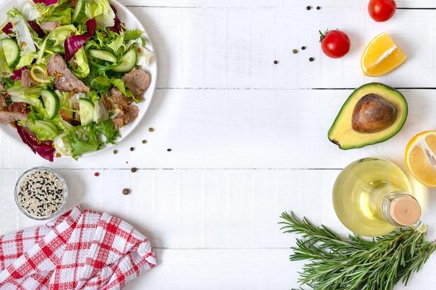 Ingredientes para cozinhar com espaço de cópia. tigela de salada fresca, alecrim, limão, especiarias e óleo na mesa de madeira branca. fundo de comida. conceito de alimentação saudável.