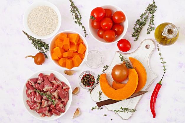 Ingredientes para cozinhar corações de frango com abóbora e tomate em molho de tomate. o enfeite é servido com arroz cozido. postura plana. vista do topo.
