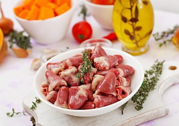 Ingredientes para cozinhar corações de frango com abóbora e tomate em molho de tomate. o enfeite é servido com arroz cozido.