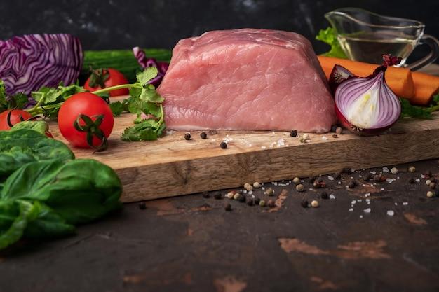 Ingredientes para cozinhar ensopado: carne crua, ervas, especiarias, legumes e sal na tábua rústica