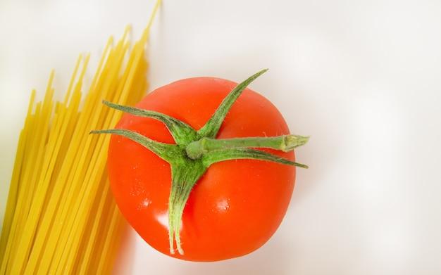Ingredientes para cozinhar espaguete e tomate macarrão-cru tradicionais, vista superior, fundo branco, cópia do espaço