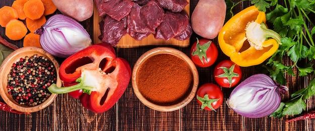 Ingredientes para cozinhar goulash ou ensopado: carne crua, ervas, especiarias, legumes na mesa de madeira escura.