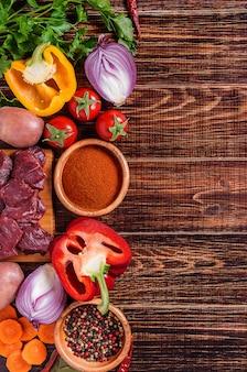Ingredientes para cozinhar goulash ou ensopado: carne crua, ervas, especiarias, legumes no escuro de madeira.