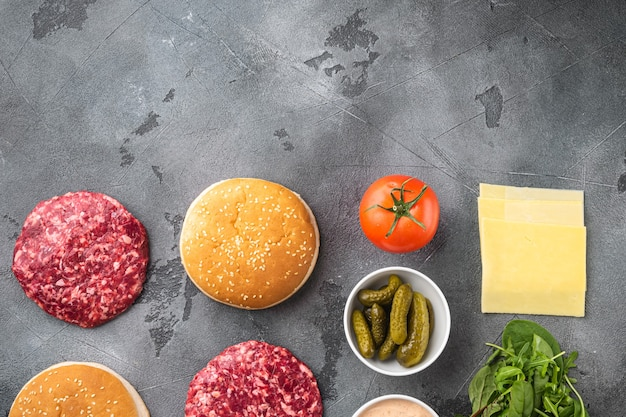 Ingredientes para cozinhar hambúrgueres. conjunto de costeletas de carne bovina moída crua, em pedra cinza