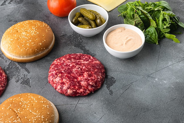 Ingredientes para cozinhar hambúrgueres. conjunto de rissóis de carne picada, pãezinhos, tomates, ervas e temperos