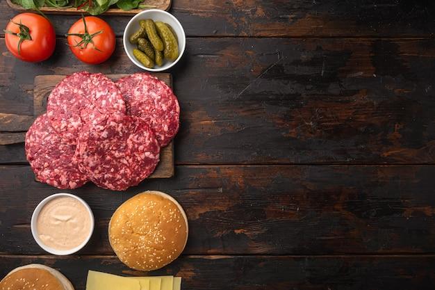 Ingredientes para cozinhar hambúrgueres. rissóis de carne picada, pãezinhos, tomates, ervas e temperos