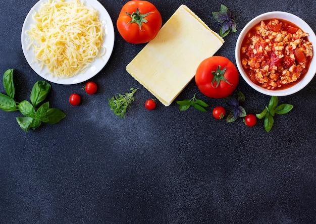 Ingredientes para cozinhar lasanha. receita de lasanha italiana caseira com molho de tomate e carne. tomate, manjericão, molho de carne, queijo mussarela, macarrão de lasanha. comida italiana. vista do topo. copie o espaço