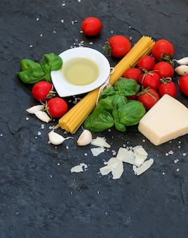 Ingredientes para cozinhar macarrão. espaguete, azeite, alho, queijo parmesão, tomate e manjericão fresco na ardósia preta, vista superior, copyspace.