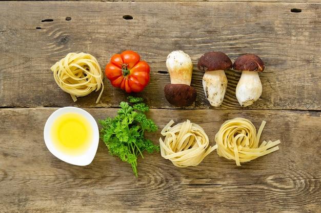 Ingredientes para cozinhar macarrão. fettuccine com cogumelos porcini, tomate e verde sobre fundo de madeira velho.