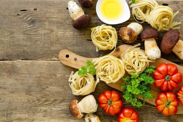 Ingredientes para cozinhar macarrão. fettuccine com cogumelos porcini, tomates e verdes em fundo de madeira velho.