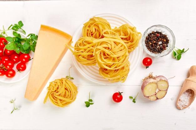 Ingredientes para cozinhar macarrão - tagliatelle, tomate, alho, manjericão, queijo parmesão na superfície plana de madeira branca leiga, vista superior, moldura, cópia espaço, conceito de comida italiana.