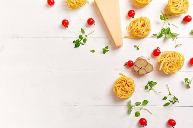 Ingredientes para cozinhar macarrão - tagliatelle, tomate, alho, manjericão, queijo parmesão sobre fundo de madeira branco plano leigo, vista superior, moldura, cópia espaço, conceito de comida italiana.