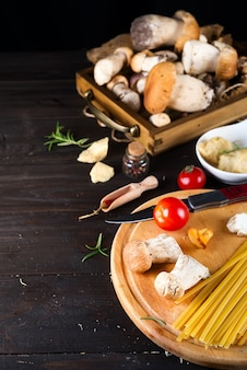 Ingredientes para cozinhar massas italianas - espaguete, tomate, cogumelos e verduras