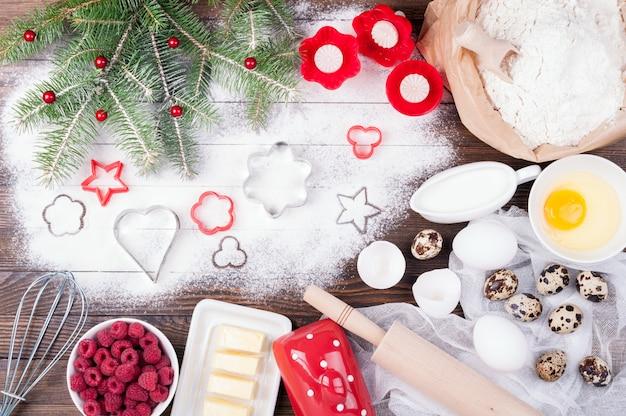 Ingredientes para cozinhar natal assando com farinha, ovos, manteiga, leite de framboesas e utensílios de cozinha