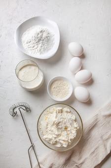 Ingredientes para cozinhar o cheesecake de são sebastião queimado espanhol basco. produtos de panificação - cream cheese, açúcar, ovos, farinha e creme em superfície clara. receita passo a passo vista superior plana.