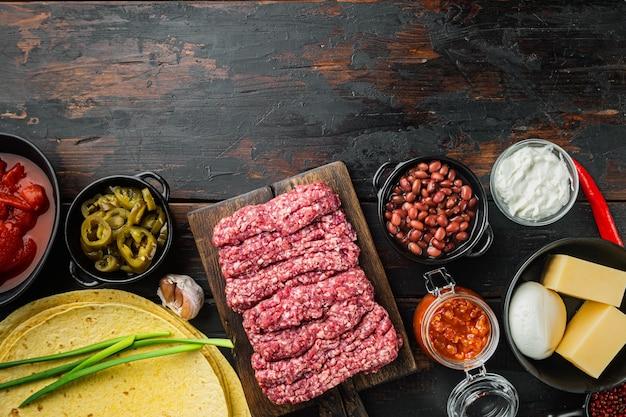 Ingredientes para cozinhar quesadillas, no fundo da velha mesa de madeira escura, vista superior