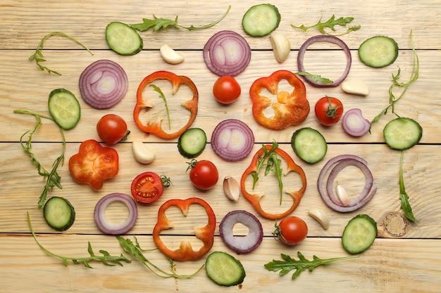 Ingredientes para cozinhar salada. fundo de vários vegetais e especiarias, cenoura, tomate, cebola, pepino, pimenta e rúcula em uma mesa de madeira natural. vista do topo.