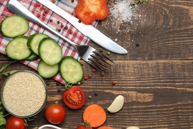 Ingredientes para cozinhar salada. vários vegetais e especiarias, cenouras, tomates, pepinos, pimentões e rúcula em uma mesa de madeira marrom. vista do topo.
