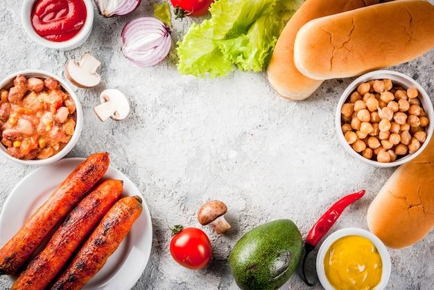 Ingredientes para diferentes caseiros vegan cenoura cachorros-quentes, com cebola frita, abacate, pimentão, cogumelos, tomate e feijão, pedra cinza copyspace vista superior