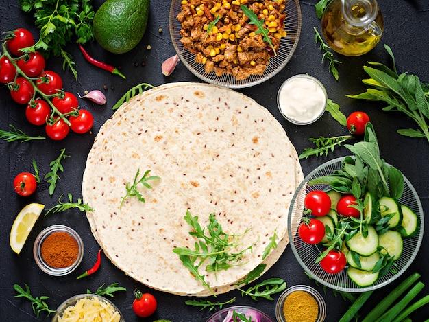 Ingredientes para envoltórios de burritos com carne e legumes em fundo preto. vista do topo