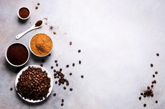 Ingredientes para fazer a bebida da cafeína - açúcar marrom do coco, feijões de café, café à terra e instantâneo no concreto claro, espaço da cópia, vista superior.