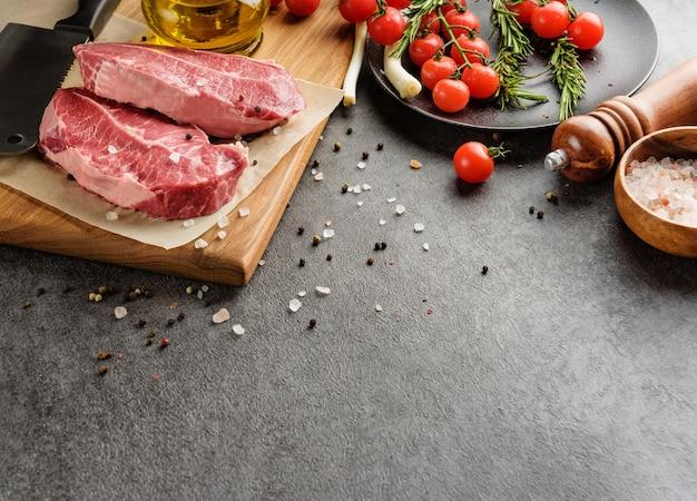 Ingredientes para fazer bife de carne, legumes e condimentos em um fundo escuro com espaço de cópia