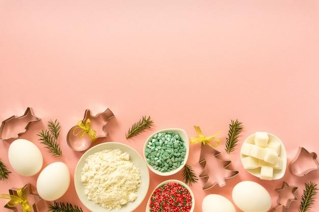 Ingredientes para fazer biscoitos de natal. ovos, farinha, açúcar e granulado doce em um fundo rosa com espaço de cópia.