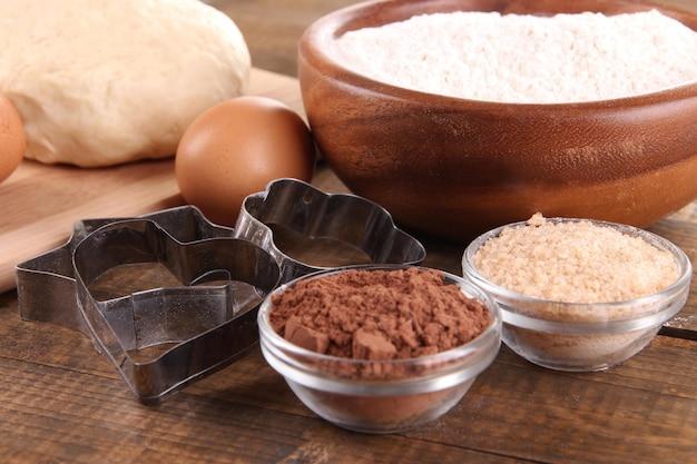 Ingredientes para fazer biscoitos em fundo de madeira