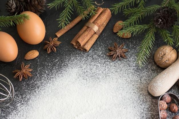 Ingredientes para fazer bolos de natal em uma pedra escura com espaço para texto.