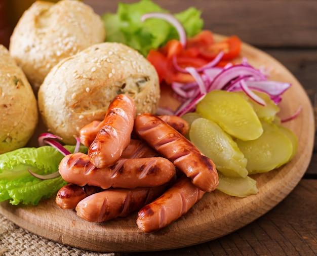 Ingredientes para fazer cachorro-quente - sanduíche com picles, cebola roxa e alface em fundo de madeira