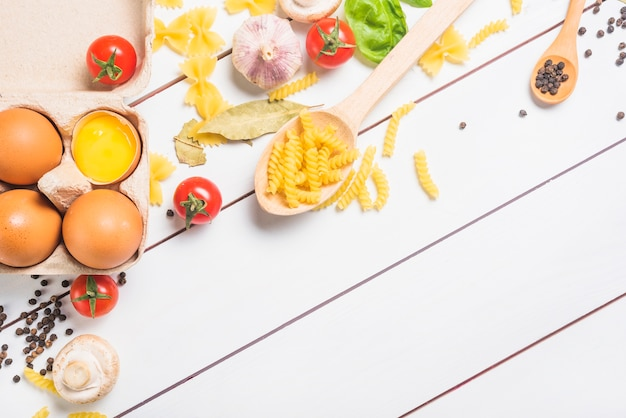 Ingredientes para fazer macarrão no pano de fundo de prancha branca