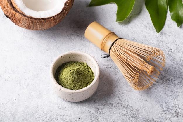 Ingredientes para fazer matcha latte, chá verde japonês com leite de coco em fundo branco.