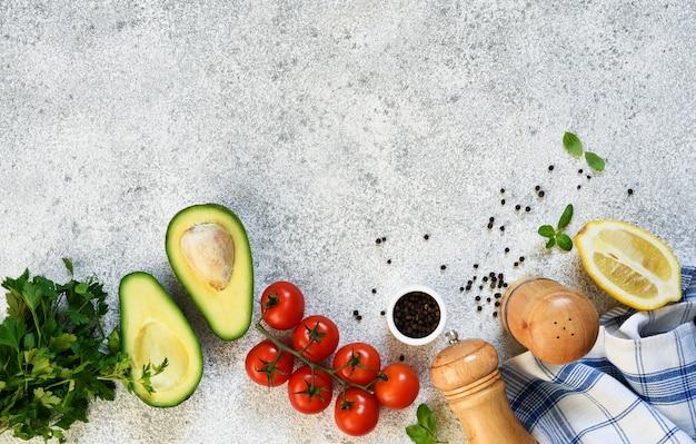 Ingredientes para fazer o molho guacamole. comida em uma mesa de concreto com espaço para texto.