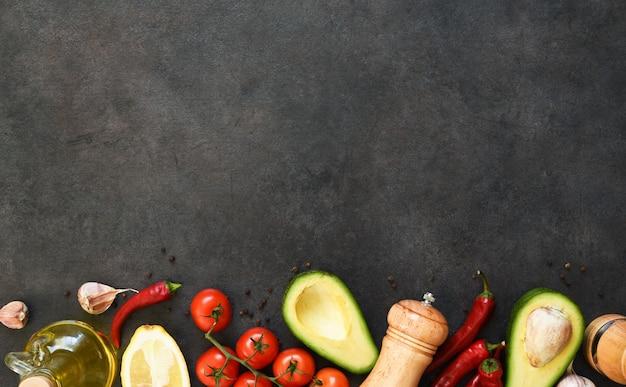Ingredientes para fazer o molho guacamole. comida em uma mesa de concreto preta com espaço para texto.