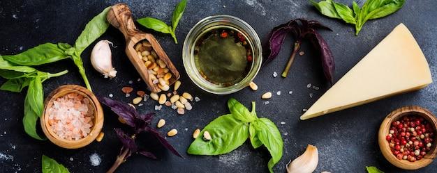 Ingredientes para fazer o molho pesto italiano tradicional em antigo fundo escuro e rústico. postura plana