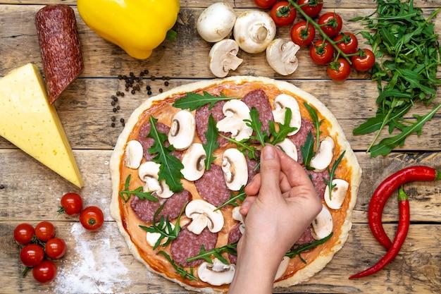 Ingredientes para fazer pizza, antes de assar, em uma mesa de madeira, vista de cima com a rúcula estendida