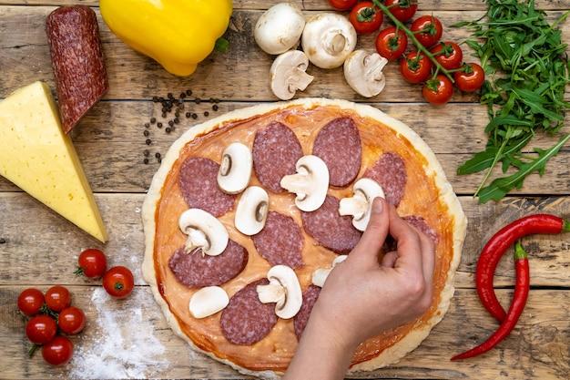 Ingredientes para fazer pizza, antes de assar, em uma mesa de madeira, vista de cima com cogumelos dispostos