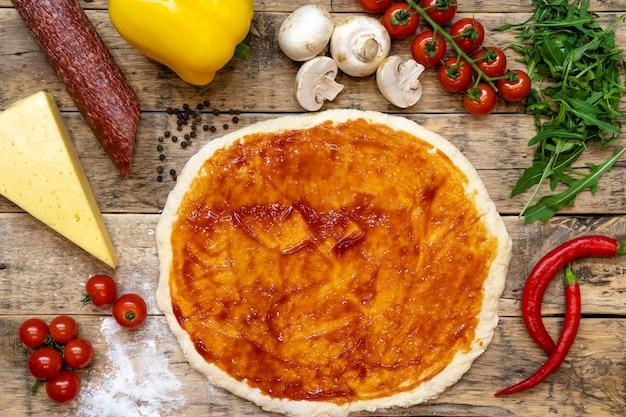 Ingredientes para fazer pizza, antes de assar, em uma mesa de madeira, vista de cima, receita passo a passo