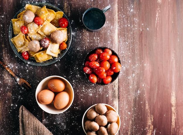 Ingredientes para fazer ravioli caseiro com molho de cogumelos em uma velha mesa de madeira. comida vegetariana italiana. copyspace