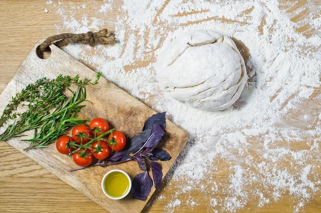 Ingredientes para focaccia: massa, tomate, alecrim, tomilho, manjericão, azeite de oliva em uma mesa de madeira.